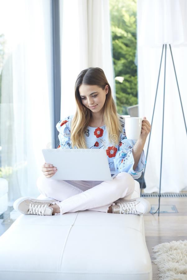 Lovely young woman using her laptop royalty free stock photography