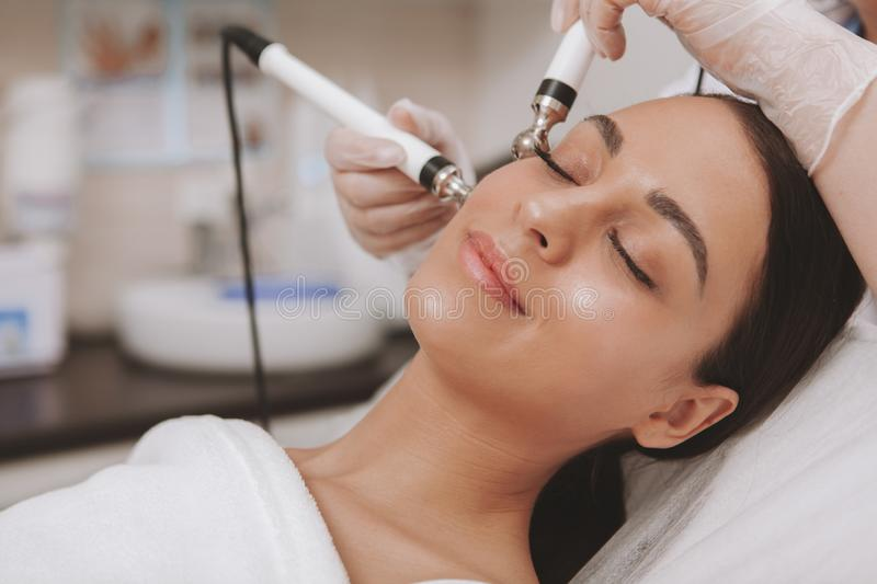 Lovely young woman visiting cosmetologist at beauty clinic stock photography