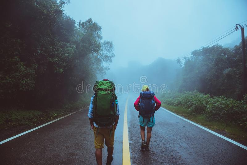 Lover asian man and asian women travel nature. Walk on the road route. traveling nature happily. Amid the mist rainy. Lover asian men and asian women travel stock photos