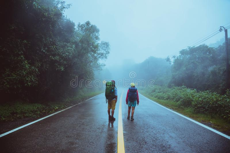 Lover asian man and asian women travel nature. Walk on the road route. traveling nature happily. Amid the mist rainy. Lover asian men and asian women travel royalty free stock image