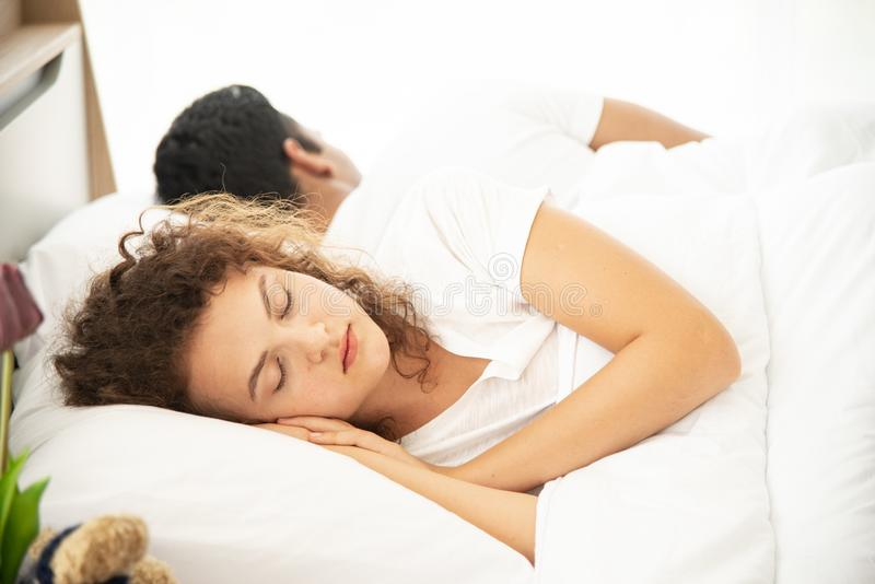 Lover concept. Young attractive couple lying under white blanket in bed stock images