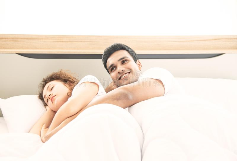 Lover concept. Young attractive couple lying under white blanket in bed stock photos