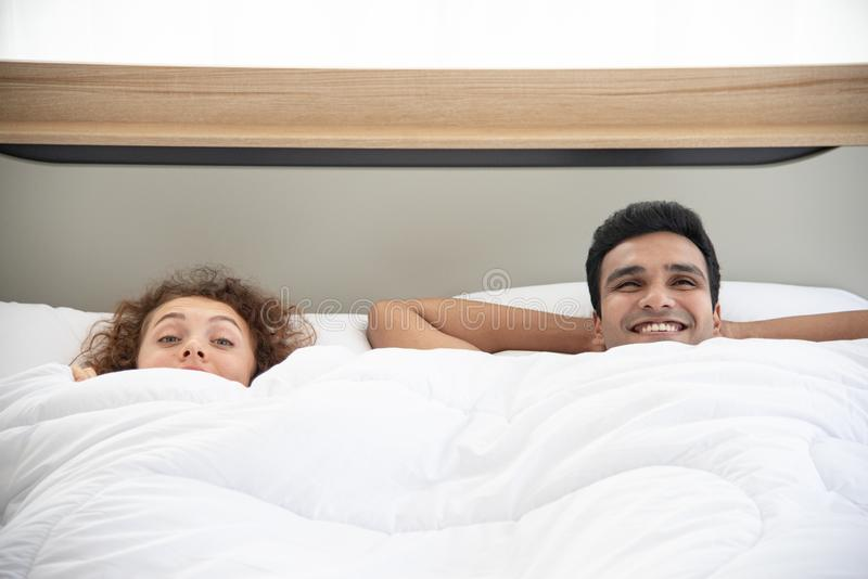 Lover concept. Young attractive couple lying under white blanket in bed stock image