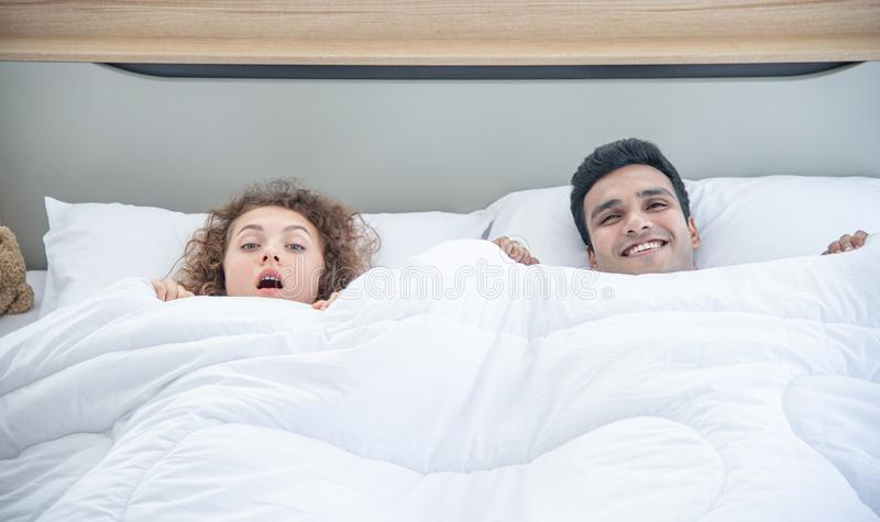 Lover concept. Young attractive couple lying under white blanket in bed stock photo
