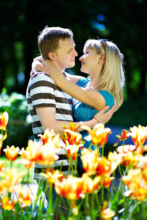 Lover man and girl among red yellow flowers royalty free stock photo