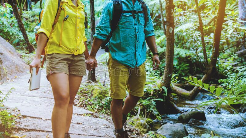 Lover woman and man asian travel nature.Travel relax. Walking and studying nature in the forest. Thailand royalty free stock image