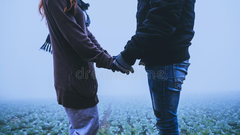Lover women and men asians travel relax in the holiday. Happy to travel in the holiday. Lovers walk hand in hand  During the foggy. Lover women and men asians stock images