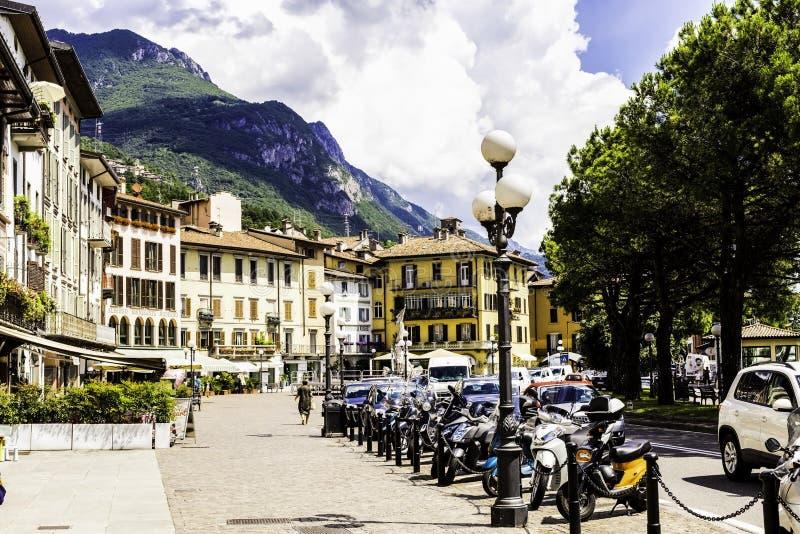 LOVERE ITALIEN, Juni 30, 2017: Hemtrevlig gata med hus, parkerade motorcyklar mot bakgrunden av härliga berg och royaltyfria bilder