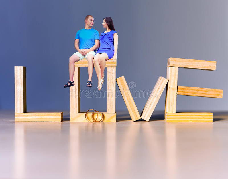Lovers at abstract background. With golden rings for proposing stock images