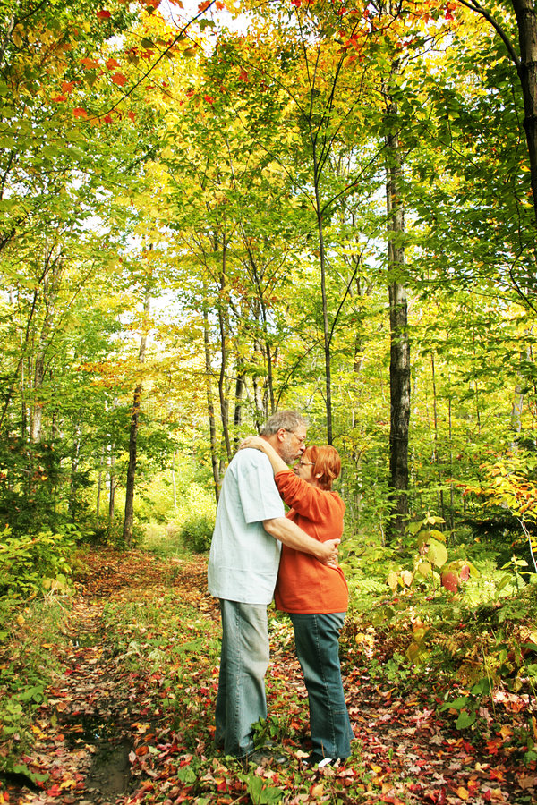 Lovers in autumn. Mature lovers kissing in a middle of a path in yellow forest. During a very nice autumn day royalty free stock photo