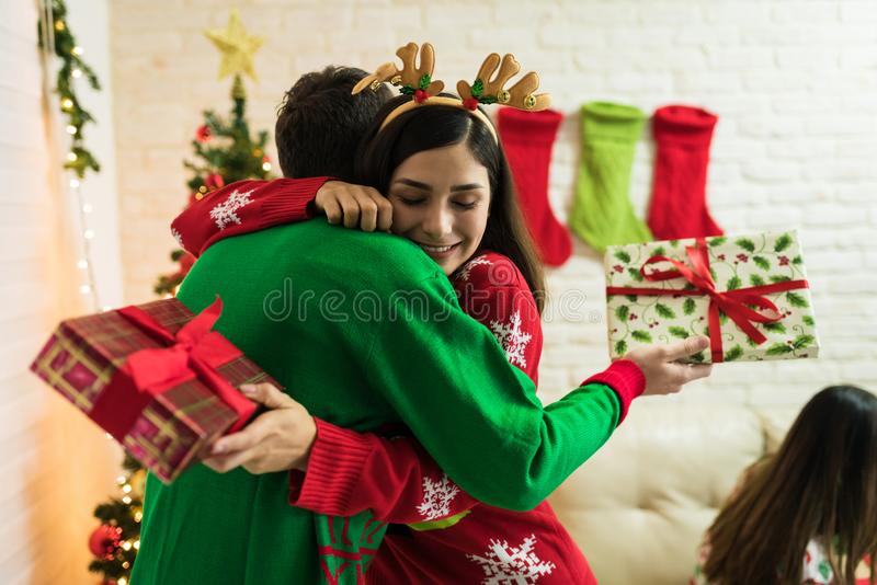Lovers Celebrating With Christmas Presents At Home. Couple embracing after exchanging presents at home during Christmas celebrations stock photos