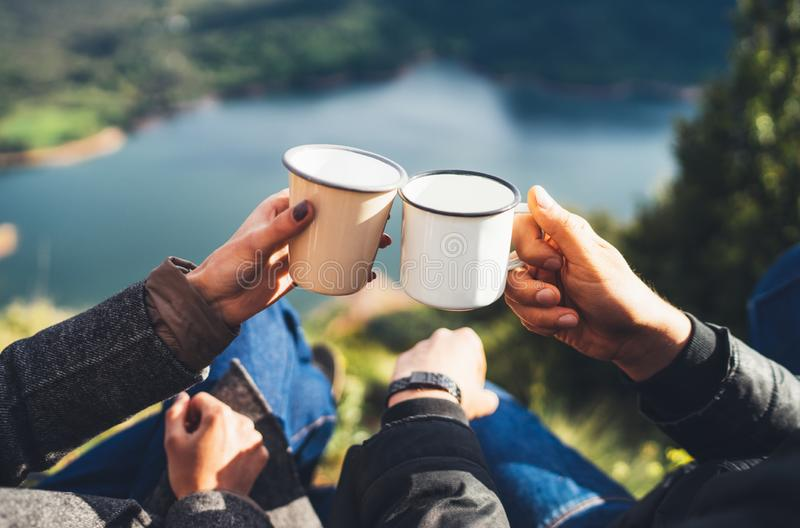 Lovers couple hold in hands mug of hot drink, enjoy together of sun flare mountain, travelers drink tea on cup on nature, romantic royalty free stock images