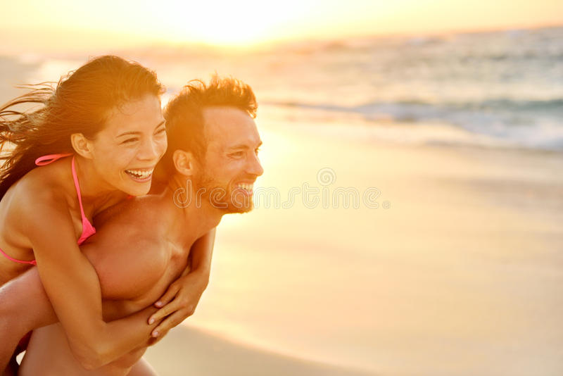Lovers couple in love having fun on beach portrait. Lovers couple in love having fun piggybacking on date on beach. Portrait beautiful healthy young adults stock photos