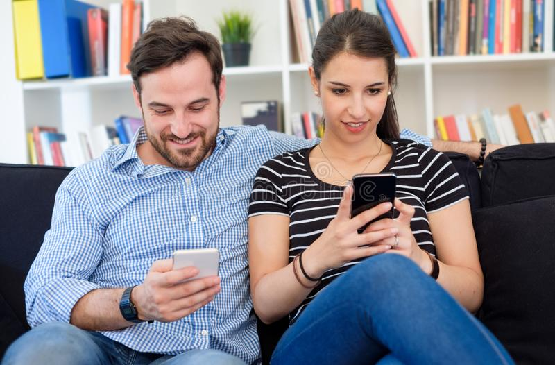 Lovers couple watching media content on mobile phone royalty free stock photography