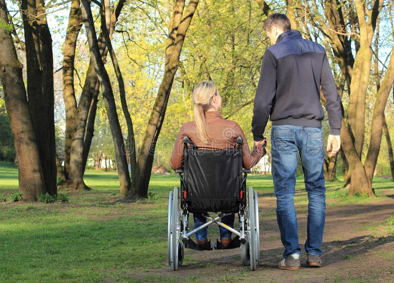 Lovers couple in wheelchair and not handicapped stock photo