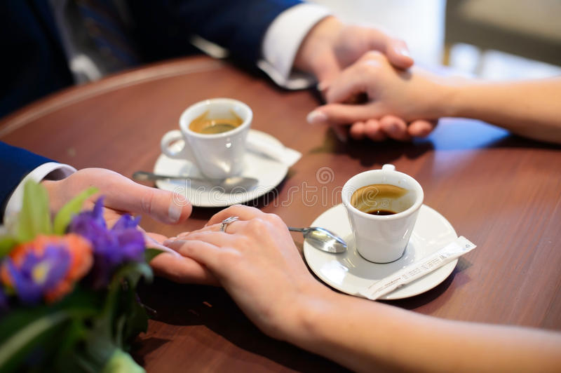 Lovers drinking coffee out of cups in the cafe. royalty free stock photos