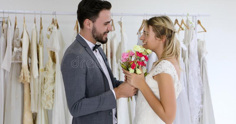 The lovers give flowers to the bride and kissed happy and couple love standing in wedding studio royalty free stock images