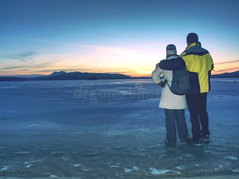 Lovers hold each other stay on ice in frozen lagoon and watch sun. Lovers hold each other stay on ice in frozen lagoon and watch rising sun at horizon. Winter royalty free stock photos