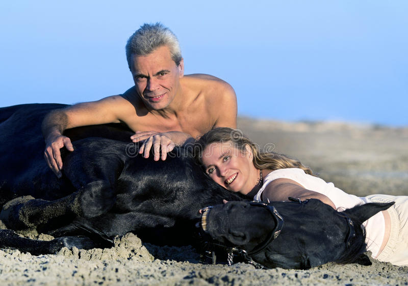 Lovers and horse. Lovers and their black stallion lying down on the beach royalty free stock photo