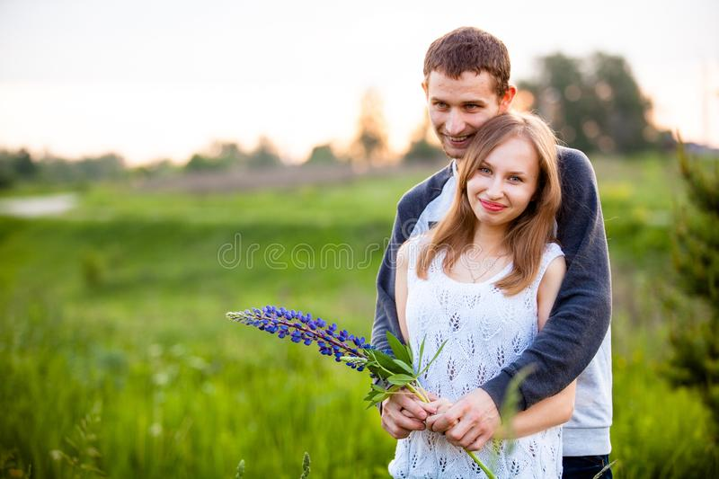 Lovers hugging in the lupins stock images