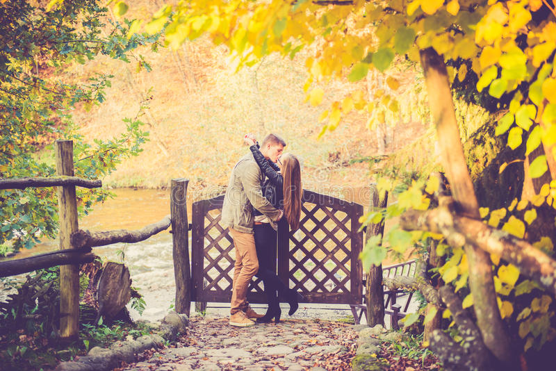 Lovers kissing in fall. Two lovers kissing near wooden fence with gates, fall or autumn background royalty free stock image