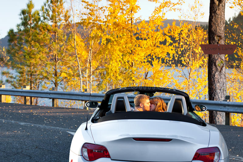 Lovers Lane. Adult young couple kissing in a convertible enjoying the sunset and autumn colors royalty free stock photo