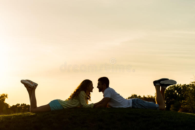 Lovers lie on the hill. Romantic meeting. Evening dating of guy and girl on top of the mountain. Honeymoon stock image
