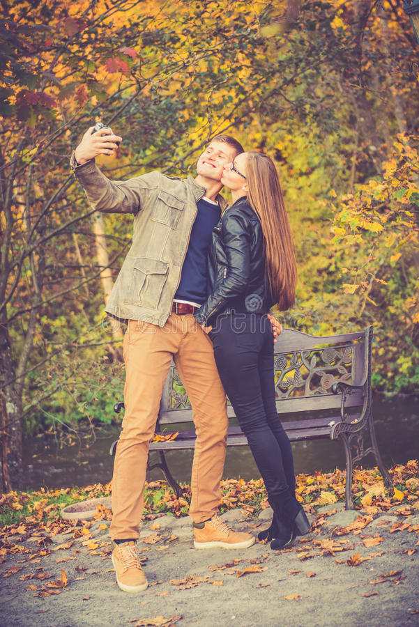 Lovers make selfie. Happy loving couple make selfie in autumn or fall park stock images