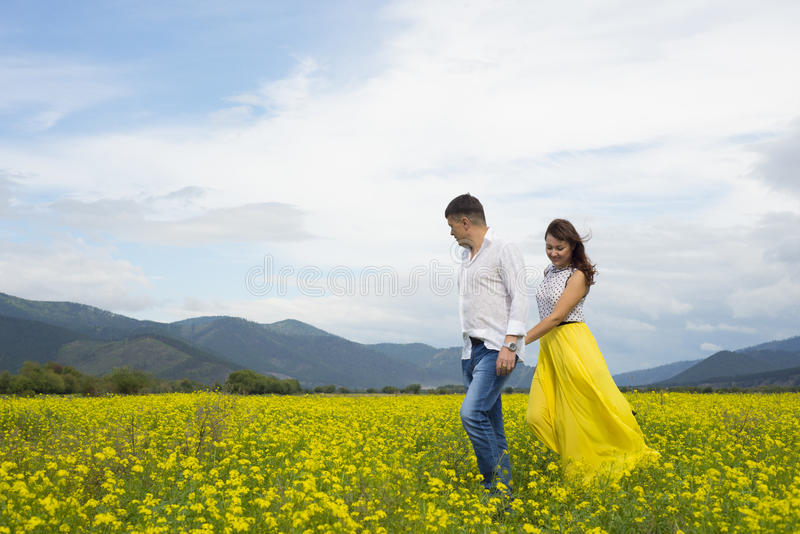 Lovers man and woman walk on the flower field. Lovers men and women walking in a flower field holding hands royalty free stock photography