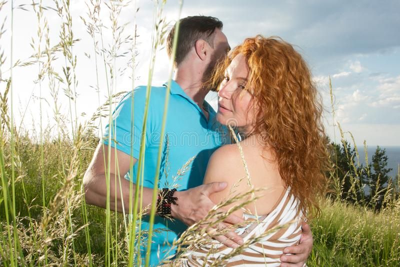 Lovers man and woman hugging. Portrait of happy middle-aged woman enjoying hug of her lover in grass. royalty free stock photos