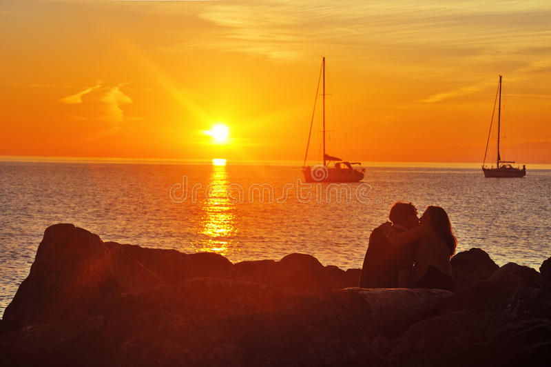 Lovers on the quay near sea at sunset. Camogli, Ligure, Italy – 07 November 2015: young couple by the sea in feelings of love. On the waterfront of the stock photos