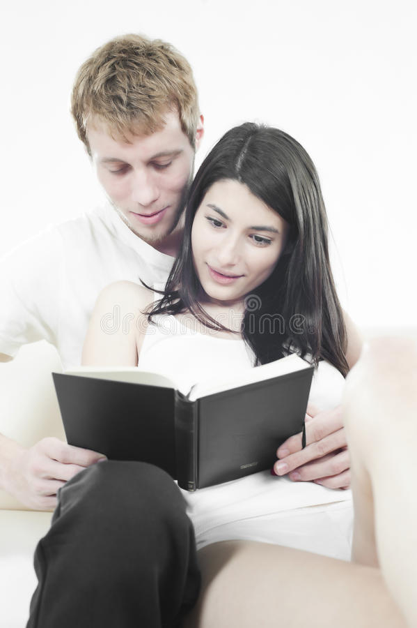 Lovers Reading A Book On Sofa Stock Photos