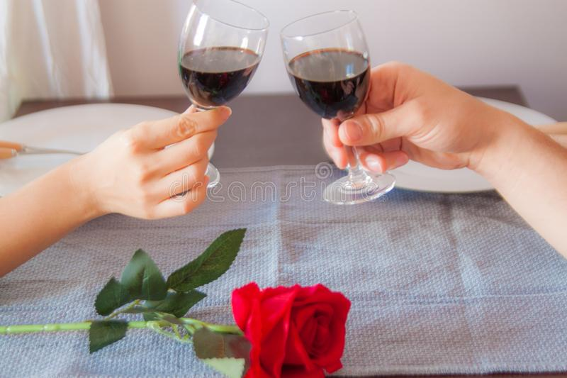 Lovers sit at a table, on the table a red rose , a glass of wine and white plates. Hands of lovers on the table, close-up. Lovers sit at a table, on the table a royalty free stock photos