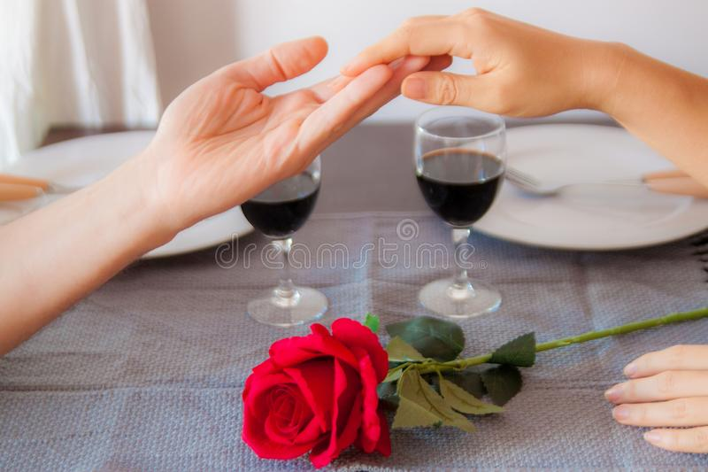 Lovers sit at a table, on the table a red rose , a glass of wine and white plates. Hands of lovers on the table, close-up. Lovers sit at a table, on the table a stock photos