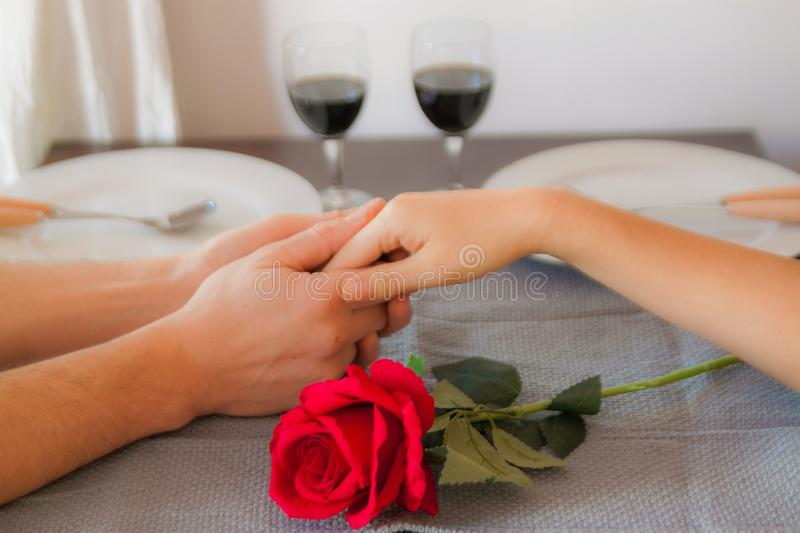 Lovers sit at a table, on the table a red rose , a glass of wine and white plates. Hands of lovers on the table, close-up. Lovers sit at a table, on the table a stock photography