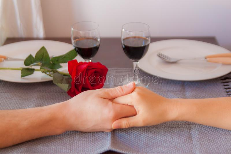 Lovers sit at a table, on the table a red rose , a glass of wine and white plates. Hands of lovers on the table, close-up. Lovers sit at a table, on the table a royalty free stock photo