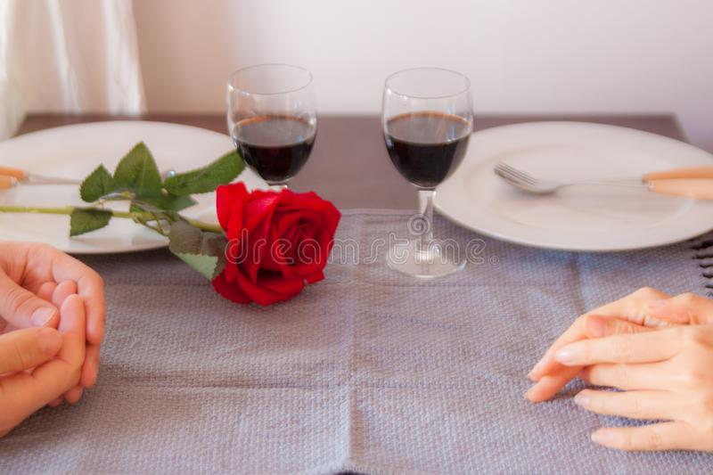 Lovers sit at a table, on the table a red rose , a glass of wine and white plates. Hands of lovers on the table, close-up. Lovers sit at a table, on the table a stock image