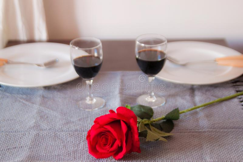 Lovers sit at a table, on the table a red rose , a glass of wine and white plates. Hands of lovers on the table, close-up. Lovers sit at a table, on the table a stock images