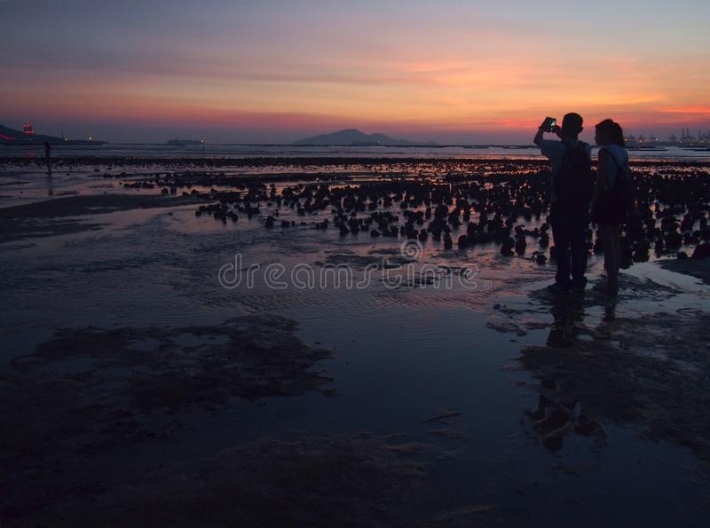 Lovers during Sunset Glow in Muddy Beach stock photos