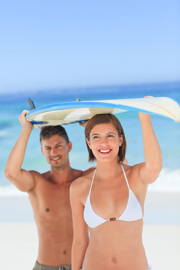 Lovers with their surfboard royalty free stock photo