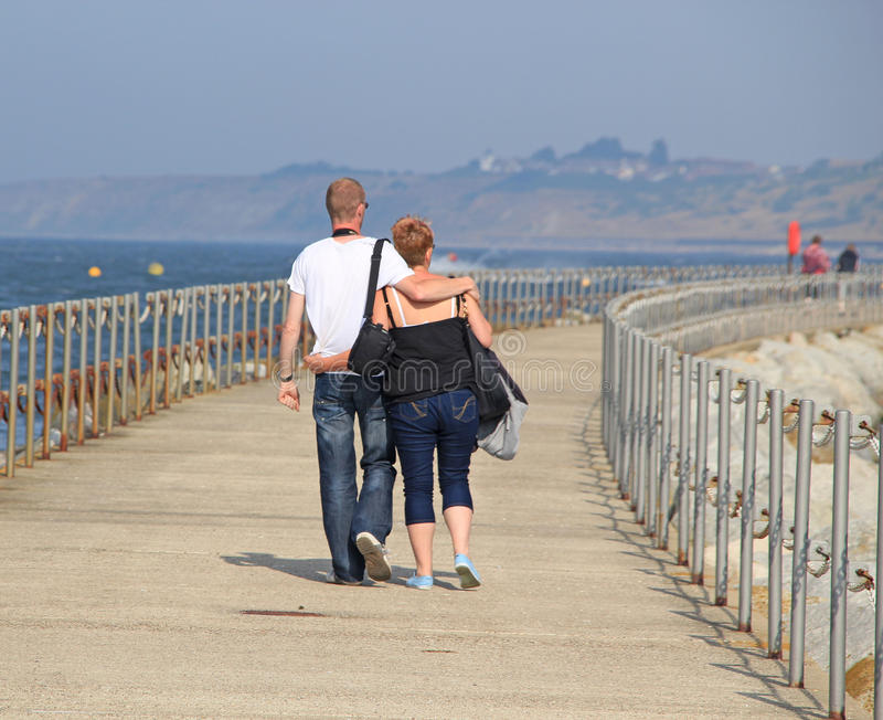 Lovers Walking Arm In Arm. This photo shows a young couple in love walking leisurely arm in arm down the Pier in Herne Bay