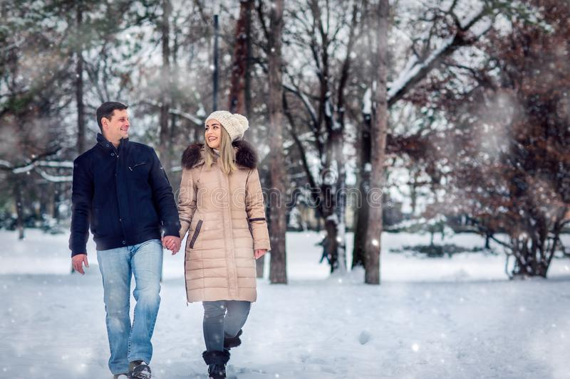 Lovers walking in winter snow- Smiling Couple in Winter Park having fun.. royalty free stock image