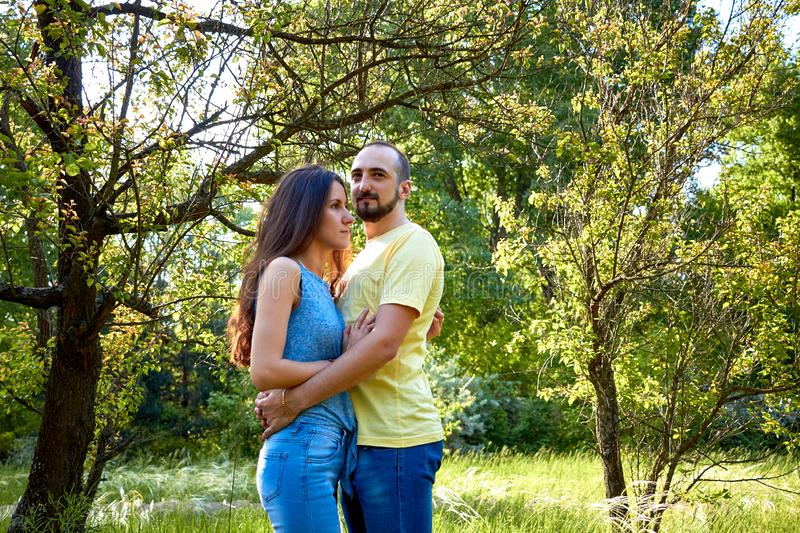 Lovers. A young couple. The guy with the girl are walking in the forest. Loving couple hugs sensually. Lovers man and woman in the royalty free stock photo