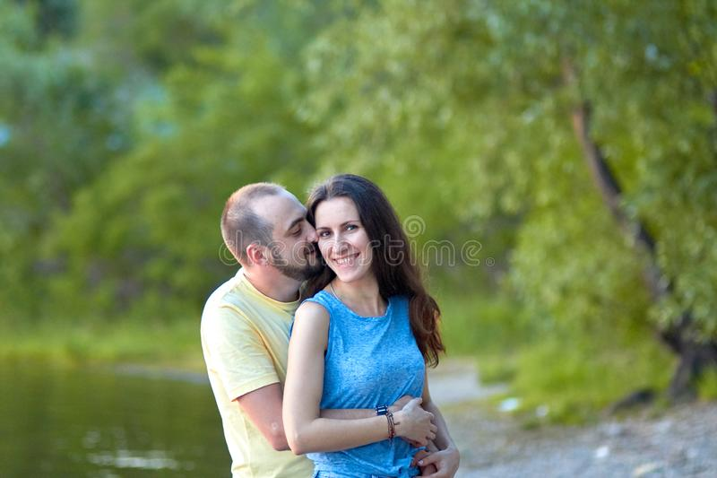 Lovers. A young couple. The guy with the girl are walking in the forest. Loving couple hugs sensually. Lovers man and woman in the stock photo