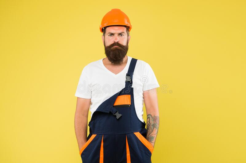 He loves his job. construction engineer in work uniform. man builder in hard hat. wear helmet for safety. expert in stock photography