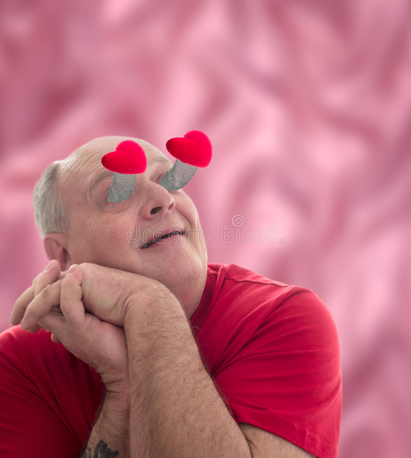 Lovestruck. An older man overcome with love, lovestuck with hearts popping out of his eyes just like the old cartoons royalty free stock photos