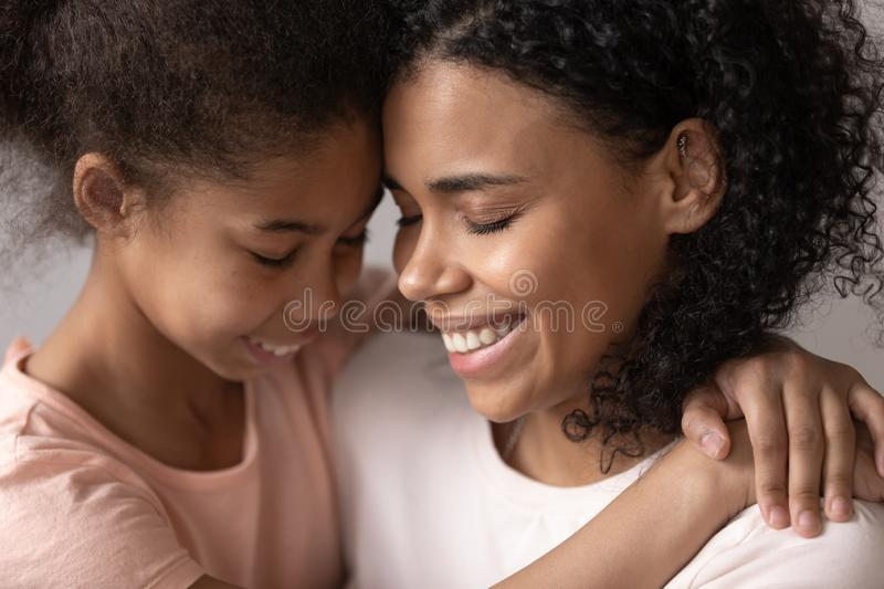 Loving affectionate african mother embrace cute little kid daughter. Feel connection enjoy time together warm relationship, happy black mum hug child girl stock photos