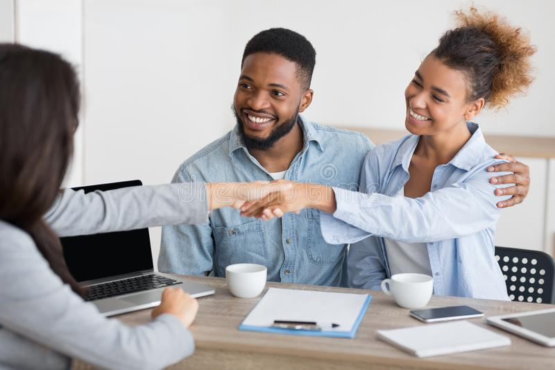 Loving african american couple and investment advisor handshaking in office. Capital planning. Happy afro spouses handshaking with financial counselor in office stock image