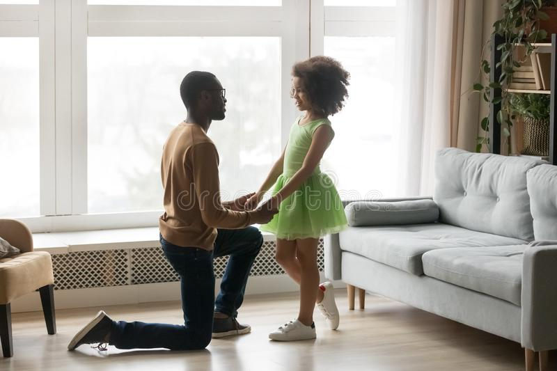 Loving African American father holding adorable preschool daughter hands. Loving African American father standing on knee, holding adorable preschool daughter stock photo