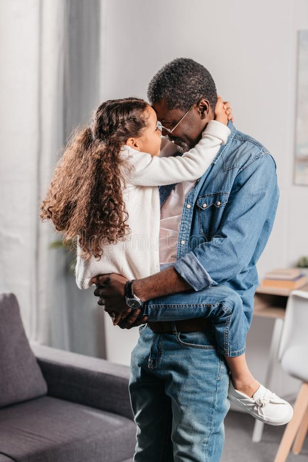 Loving african american girl embrace father that holding her. On hands royalty free stock images